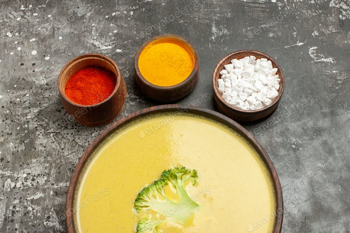 Broccoli soup in a brown bowl and different spices on gray table