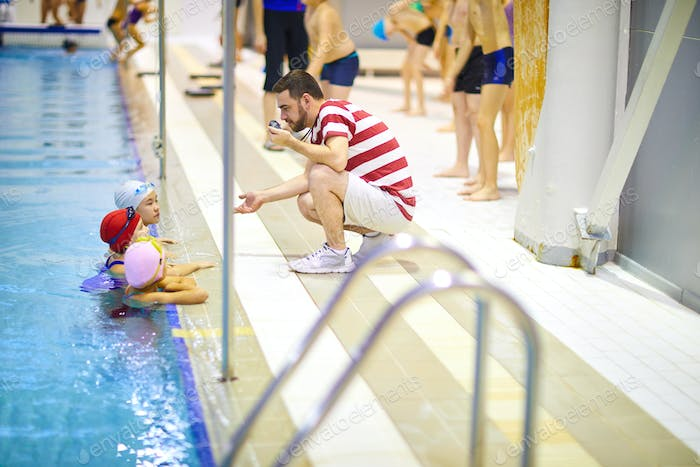 Swimming lesson with trainer in pool