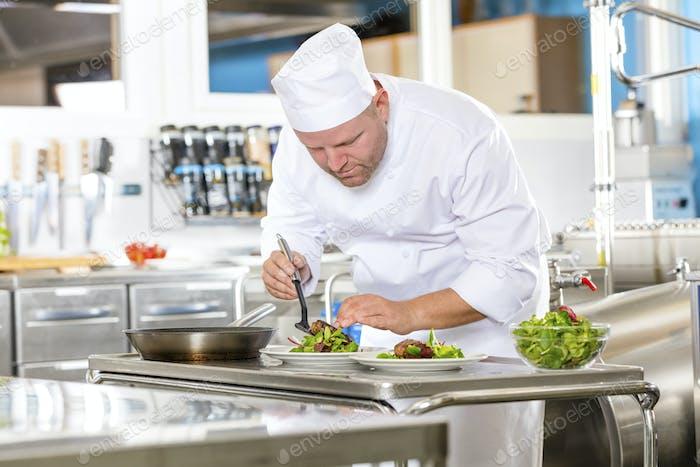 Chef bereitet Steakgericht in Gourmet-Restaurant-Küche