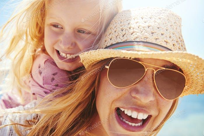 riendo joven madre y hija al aire libre