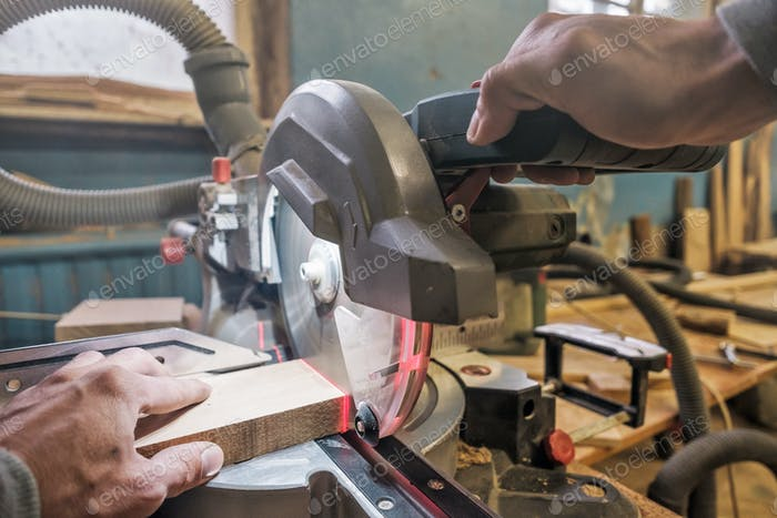 Caucasian man carpenter worker working driving circular saw to cut boards