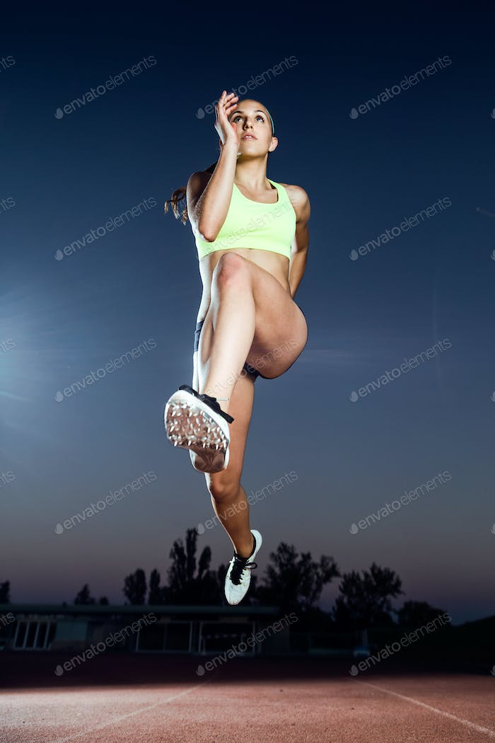 Fit young woman running on track field at night.