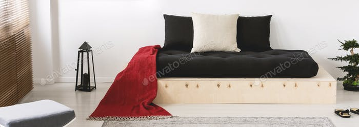 Cushions and red blanket on wooden bed in japanese bedroom inter