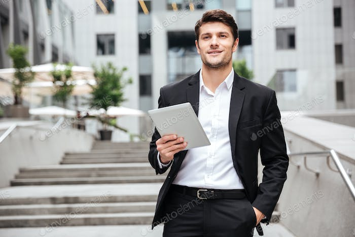 Happy businessman with tablet walking in the city