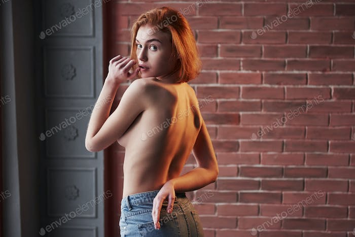 Looking back. Hot young blonde with bare chest and jeans stands against the brick wall