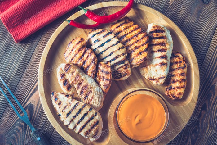 Grilled chicken breast on the wooden tray