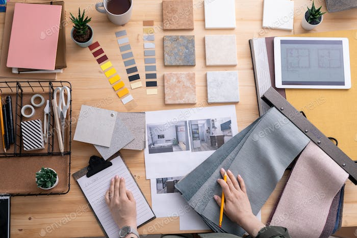 Flat lay of hands of contemporary creative interior designer over workplace