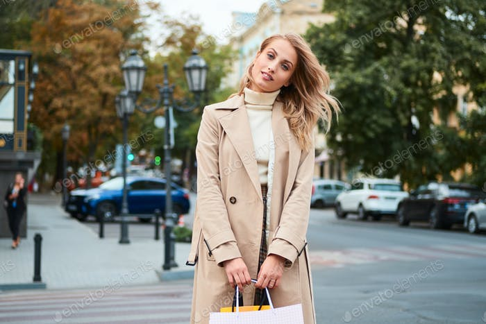 Stylish blond girl in trench coat with shopping bags happily looking in camera on city street