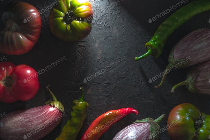 Frame of chili, multi-colored tomatoes and aubergine on a gray table free space