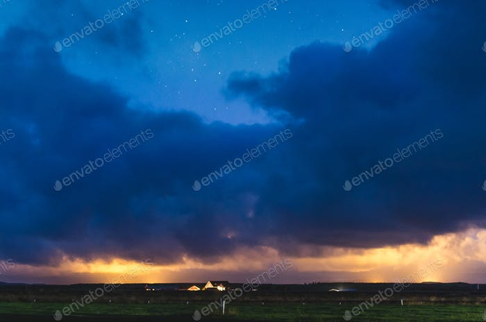 house under heavy clouds and northern lights