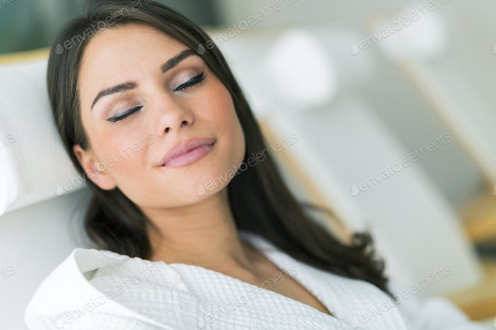 Portrait of a beautiful young woman relaxing in a robe