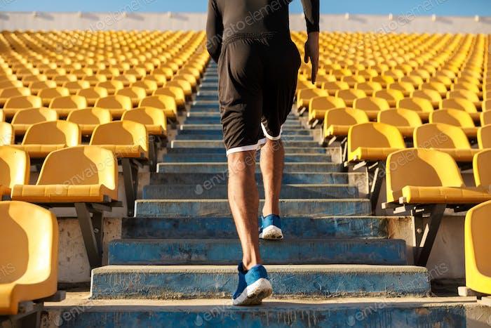 Nahaufnahme Rückansicht des jungen Sportlers läuft unter leeren Stadionsitzen