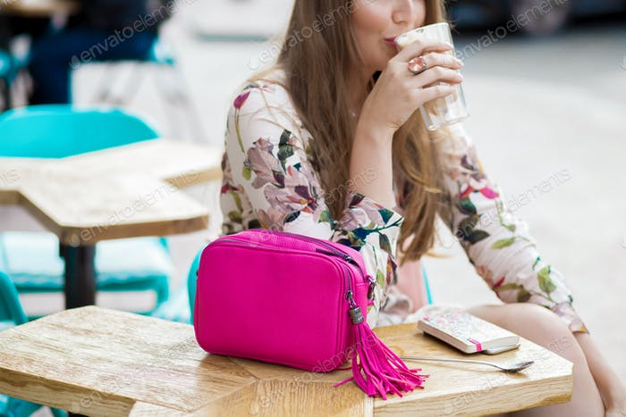 happy trendy young hipster stylish woman sitting at table in cafe