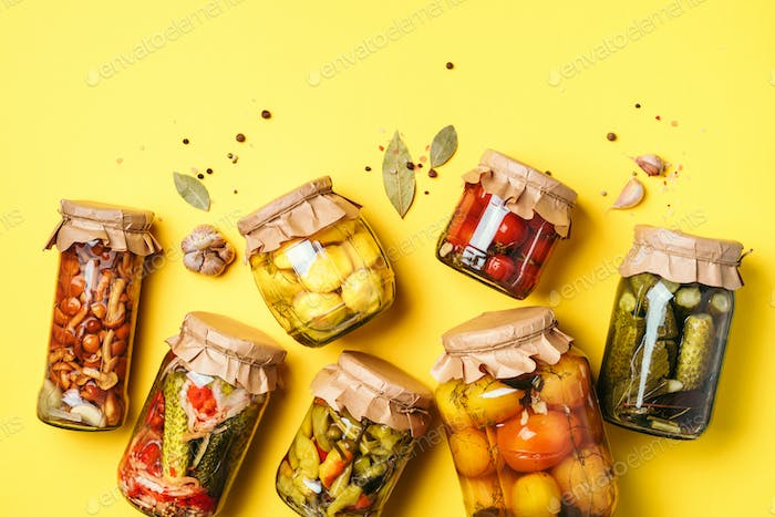Canned and preserved vegetables in glass jars over yellow background. Top view. Flat lay. Copy space