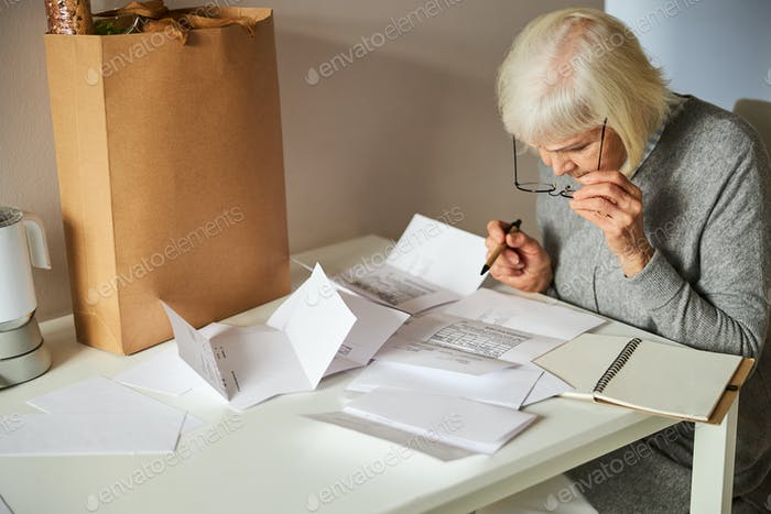 Serious pensioner leaning over an electricity bill