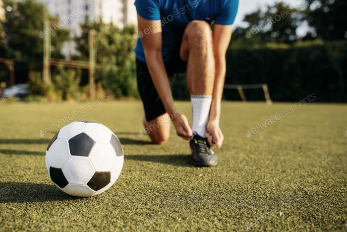Male soccer player ties his shoelaces on boots