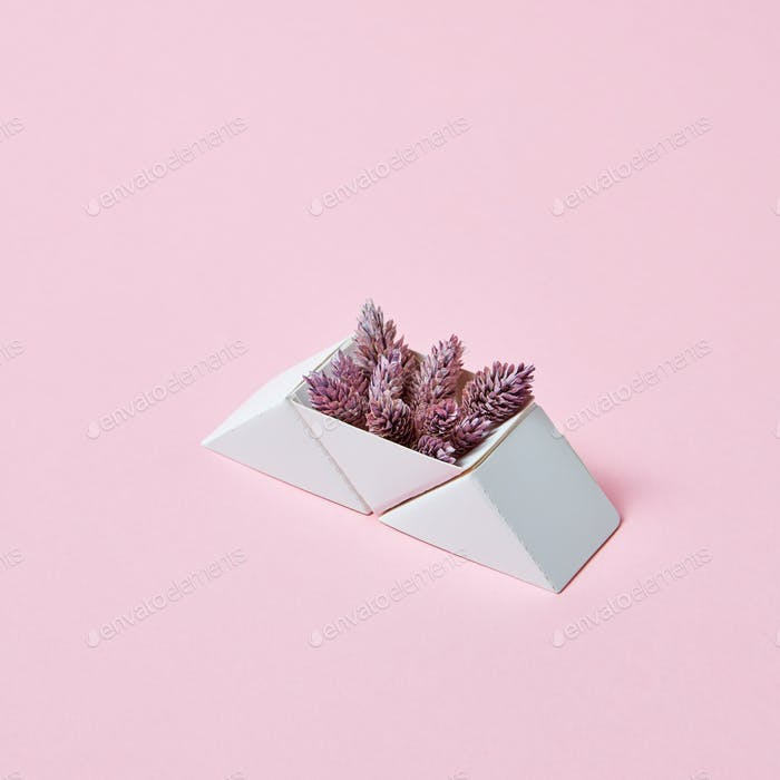 Composition of paper triangular boxes with cones on a pink background with copy space. Layout for