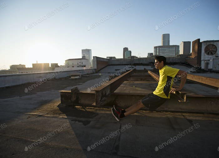 A man in exercise clothes on a rooftop overlooking the city, doing bench shoulder push ups.