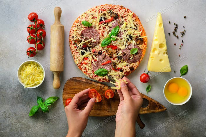 Girl hands making, decopating, preparing pizza with basil leaves on light grey background. Top view