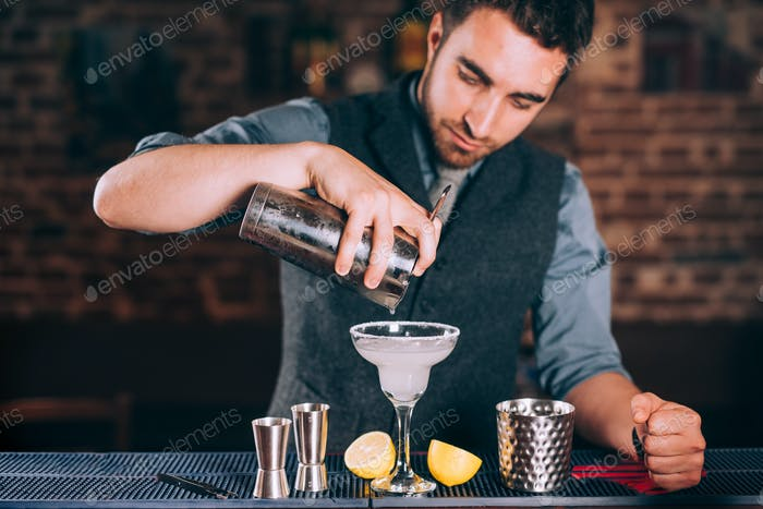 Portrait of barman pouring fresh lime margarita in fancy glass at restaurant