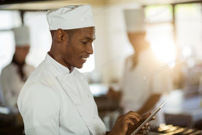 Smiling chef using digital tablet