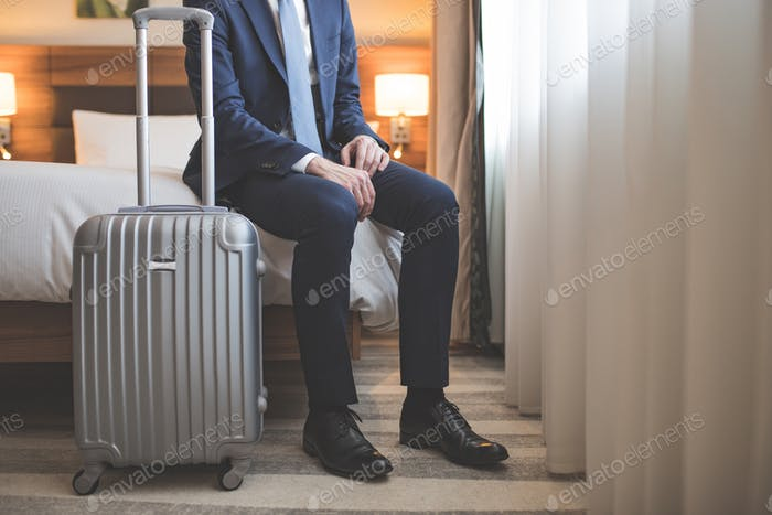 Young businessman in suit with a suitcase