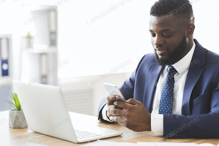 Handsome businessman using cellphone at workplace, sending email