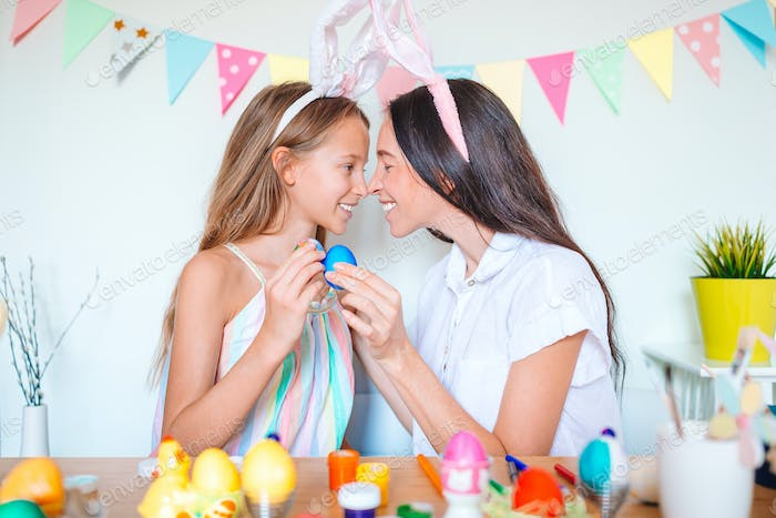 Mother and her little daughter painting eggs. Happy family preparing for Easter