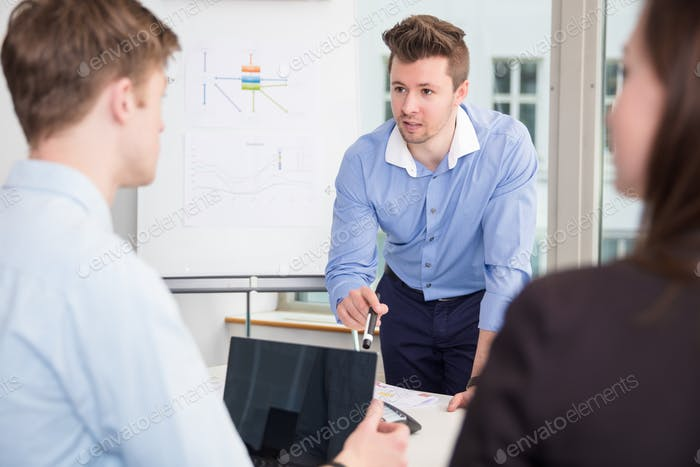 Businessman Communicating With Colleagues In Meeting at Office