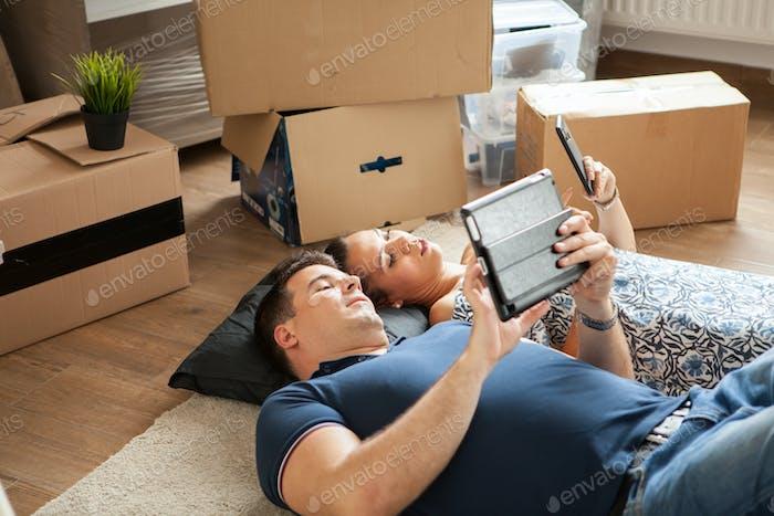 Glückliches junges Paar auf dem Boden in der Nähe von Umzugskisten liegend.