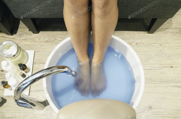Woman taking a foot spa, elevated view.