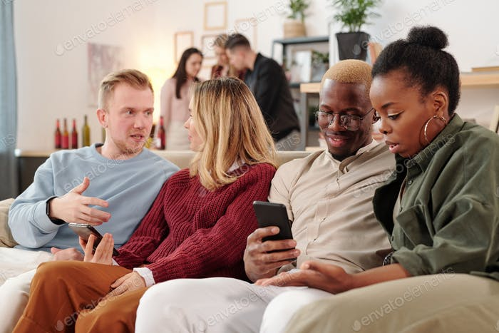 Two young intercultural couples discussing photos in smartphones at home party