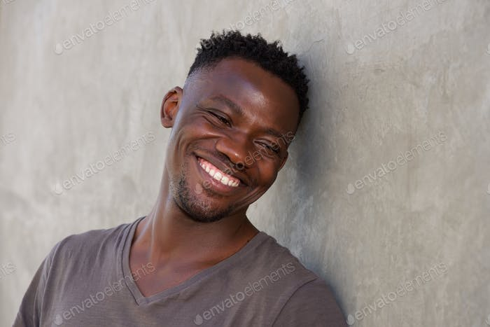 happy young african man leaning against wall