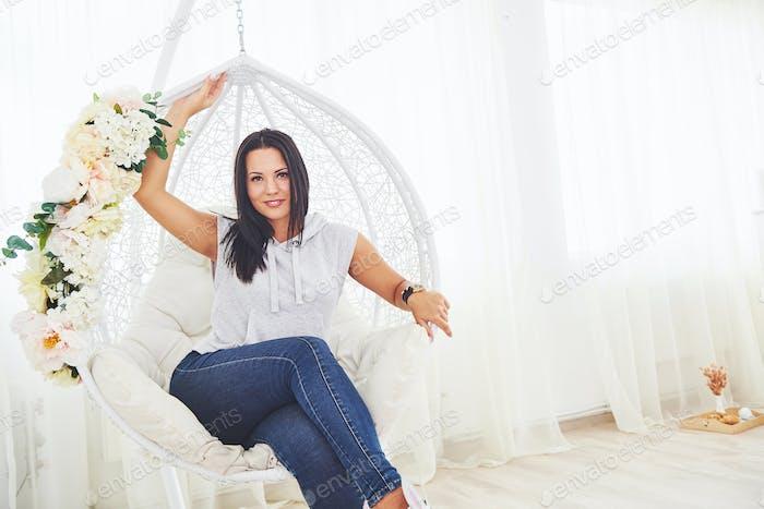 Schönes Mädchen sitzt in einem weißen Hängesessel
