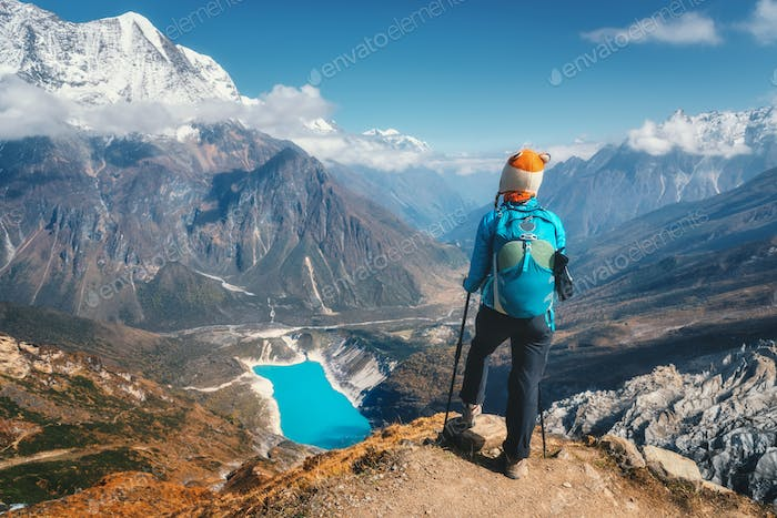 Standing woman with backpack on the mountain peak