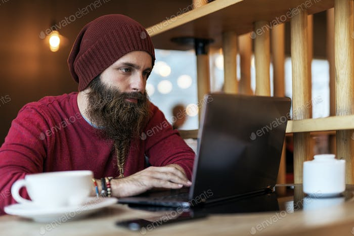 Bearded hipster typing on laptop