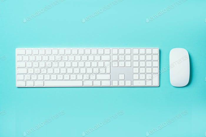 White mouse and keyboard on blue background. Top view. Copy space. Flat lay. Remote job, work. Home