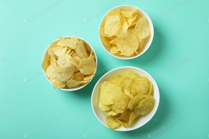 Bowls with potato chips on mint background