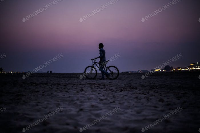 Silhouette of boy pushing a bicycle on the banks of a river at sunset.