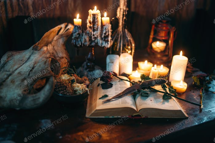 Witchcraft, dark magic, candles with ritual book