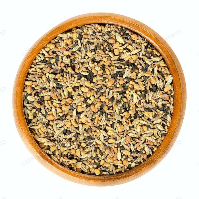 Panch phoron, whole spice blend in wooden bowl over white