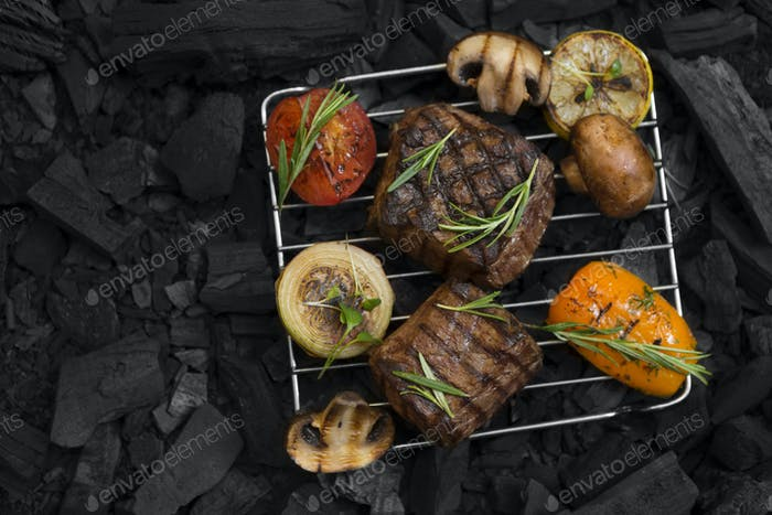 Flat lay of well done meat steak with vegetables on coals