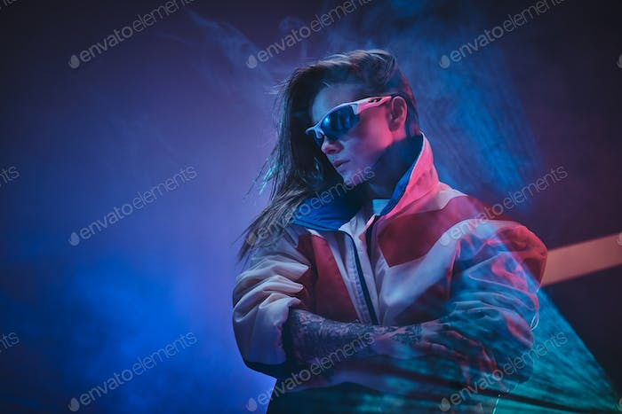 Inked attractive female posing in a neon vivid lights of a studio surrounded by smoke