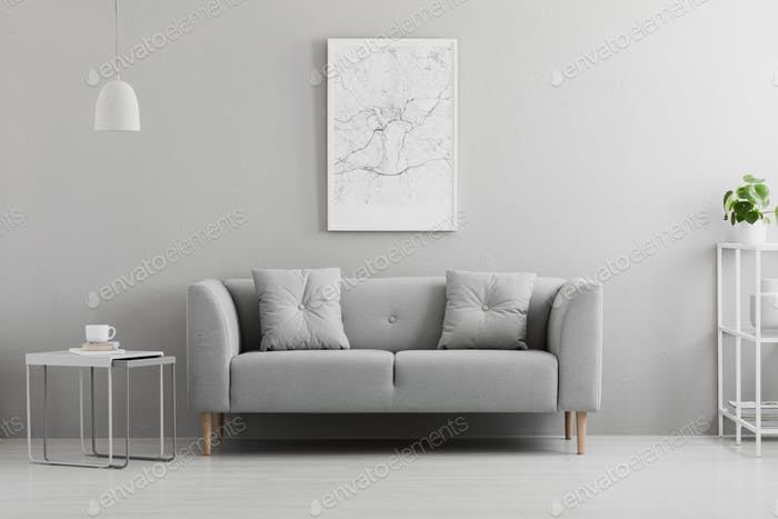 Poster above grey couch in minimal living room interior with lam