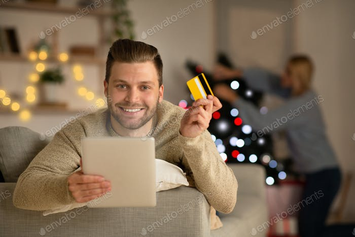 Smiling man buying Christmas gift for his wife online