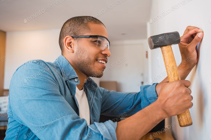 Latin man hammering nail on the wall.