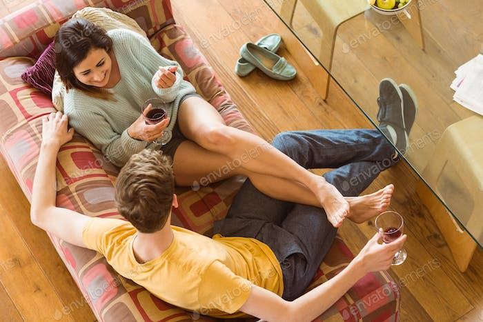 Young couple enjoying red wine on the couch at home in the living room