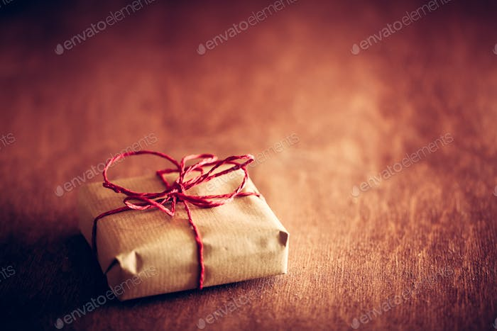 Rustic retro gift, present box with red ribbon. Christmas time