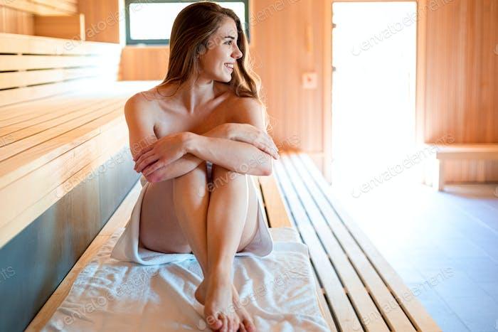 Beautiful woman in white towel relaxing in sauna