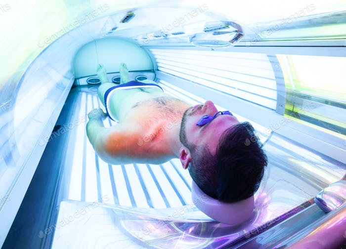 Young Man At Solarium In Beauty Salon.